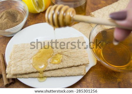 Honey and cinnamon in glass vessels on a table with a dipper and biscuits