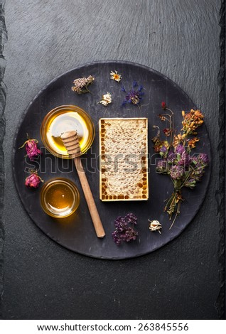 honey and dried herbs on  stone black background. top view - stock photo