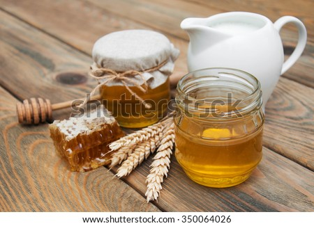 honey and milk on a old wooden background - stock photo