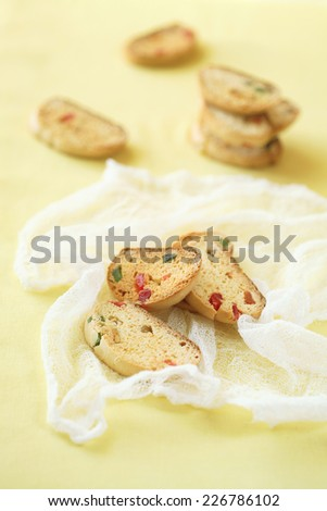 Honey and Orange Biscotti with Candied Fruits on yellow background. - stock photo