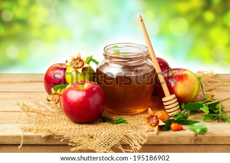 Honey, apple and pomegranate on wooden table over bokeh background - stock photo