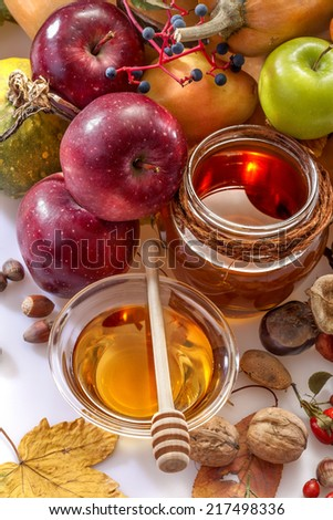 Honey, apples and autumn fruits on the white background - stock photo