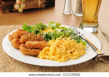 Honey battered chicken strips with macaroni and cheese and salad - stock photo