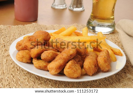 Honey battered chicken tenders with beer and french fries - stock photo