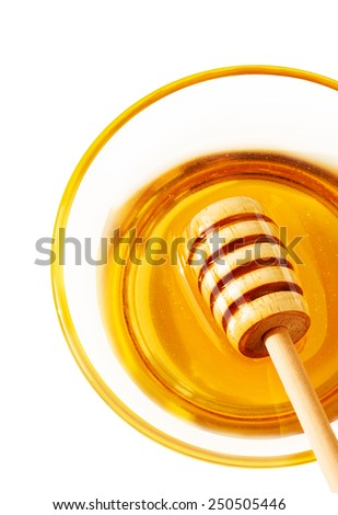Honey dipper in a transparent bowl isolated on white background - close up from above. - stock photo
