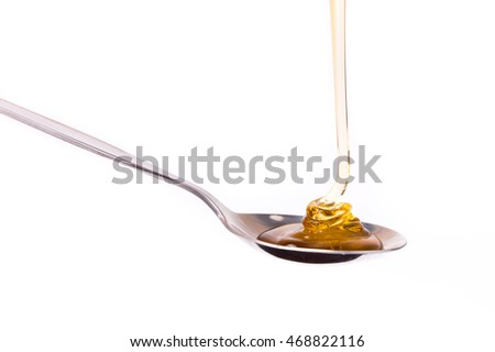 Honey dripping from a spoon isolated on white background
