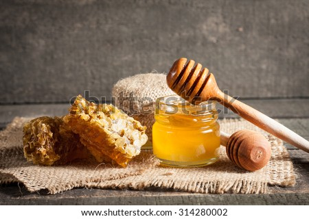 Honey dripping from a wooden honey dipper in a jar on wooden grey rustic background - stock photo