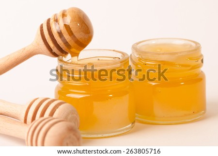 Honey dripping from a wooden honey dipper isolated on white background - stock photo