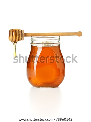 honey dripping from drizzler on top of jar, isolated on white background - stock photo