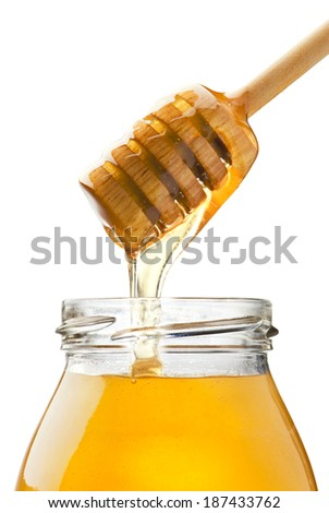 Honey drizzling from honey dipper into jar - stock photo