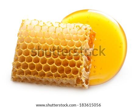 Honey drop and honeycomb on white background. - stock photo