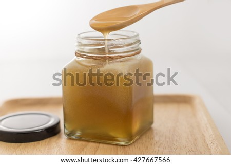 Honey droplets flowing from wooden spoon on white background
