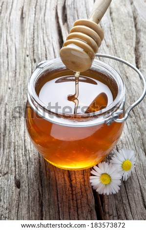 honey falling from the stick to the glass jar - stock photo