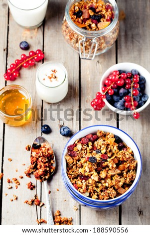 Honey glazed oatmeal, nut and flax seeds granola in a ceramic bowl with honey, yogurt and fresh berries  on a wooden background - stock photo