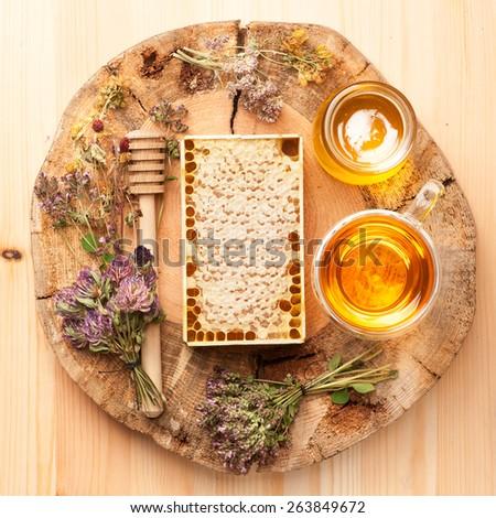 honey honeycomb, herbal tea and dried herbs. top view  - stock photo