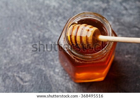 Honey in a pot or jar on kitchen table, top view - stock photo