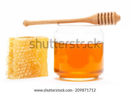 Honey in glass jar with wooden dipper and honeycomb on white isolated background - stock photo