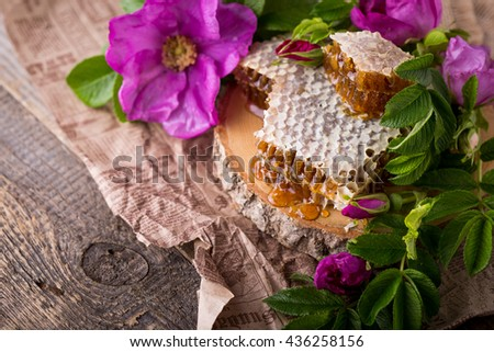 Honey in honeycombs. A dogrose rose decor on a background. Darc of a photo