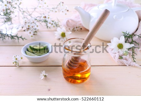 Honey in jar with dipper, tea pot, lime slices and white chrysanthemum flowers.