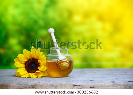 Honey in jar with honey dipper and sunflower on wooden background - stock photo