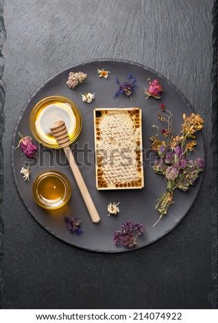 Honey jar, honeycomb and dried herbs  - stock photo
