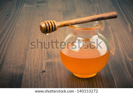 Honey jar on wooden table. Vintage toned - stock photo