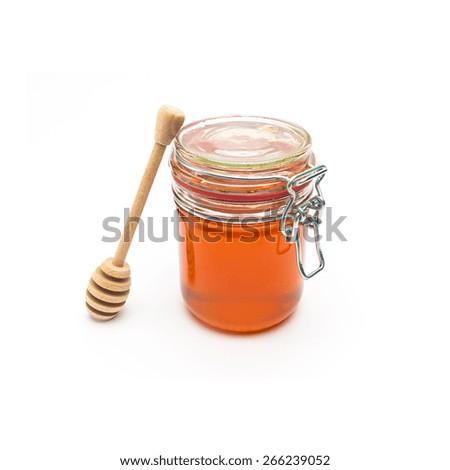 Honey jar with honey dipper - stock photo