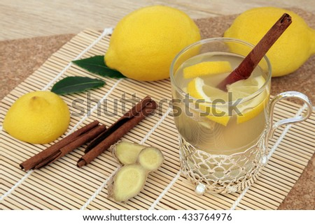 Honey, lemon, cinnamon and ginger spice drink for cold and flu relief with silver and glass mug with fresh fruit on   a bamboo mat over cork background. Selective focus. - stock photo