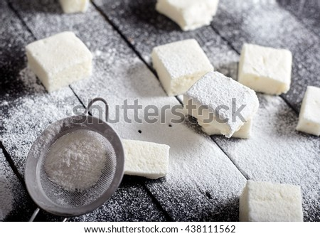 Honey marshmallows with sugar powder on a black background. The jar with marshallows on back. - stock photo