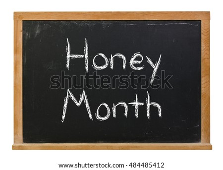 Honey Month written in white chalk on a black chalkboard isolated on white