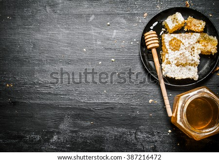 Honey style. A jar of natural honey and honey comb in the pan. On black rustic background. - stock photo