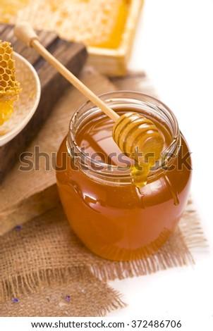 Honey tidbit in glass jar and honeycombs - stock photo