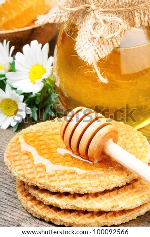 Honey waffles and wooden drizzler - stock photo