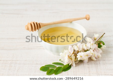 honey with acacia blossoms on a white wooden background - stock photo