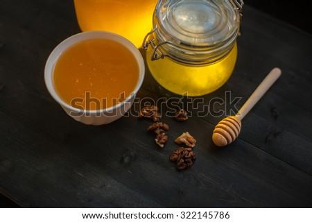 Honey with walnut on wooden background - stock photo