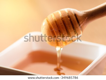 Honey with wooden honey dipper and ceramic bowl - stock photo