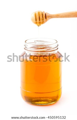 Honey with wooden honey dipper in jar on white background