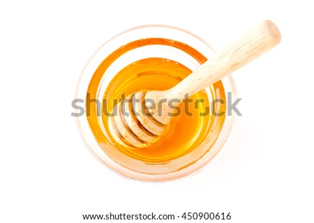 Honey with wooden honey dipper in small bowl on wooden table - stock photo