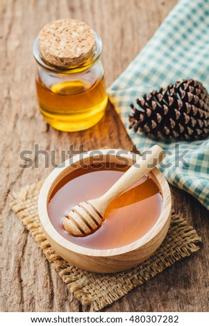 Honey with wooden honey dipper in wooden bowl on wooden table