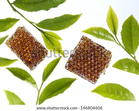 honeycomb and green tea leaves - stock photo
