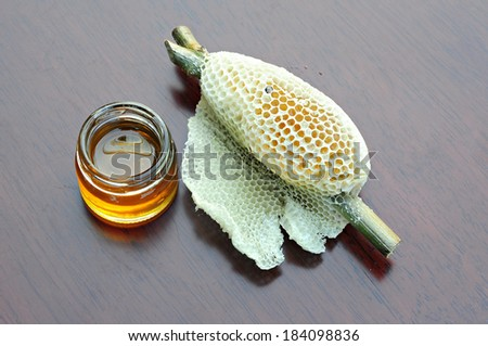 Honeycomb and Honey in glass jar Placed on wood - stock photo