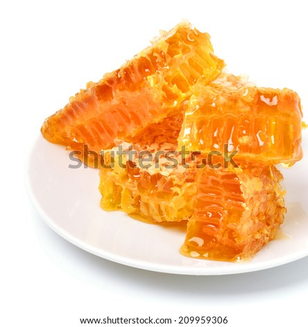Honeycomb close on the plate isolated on white - stock photo