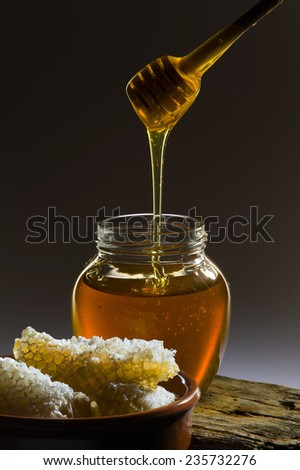 Honeycomb, honey and honey wooden stick - stock photo