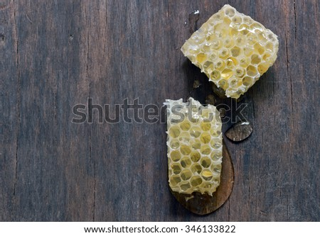 Honeycomb with honey over old wooden table - stock photo