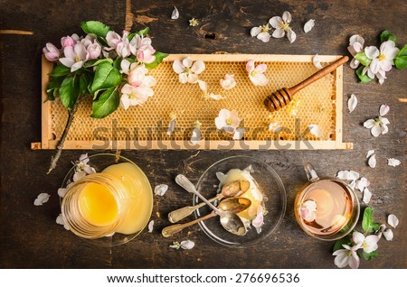 honeycomb with wooden dipper and fresh blossom,  jar with honey and plate with vintage spoons on dark rustic background, top view - stock photo