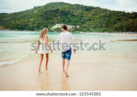 Honeymoon at the sea. Back view of loving couple walking away  at sandy beach - stock photo
