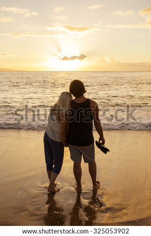 Honeymoon Couple in love watching a sunset at the beach together - stock photo