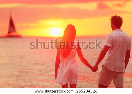 Honeymoon couple romantic in love holding hands at beach sunset. Newlywed happy young couple enjoying ocean sunset during travel holidays vacation getaway. Interracial couple. - stock photo