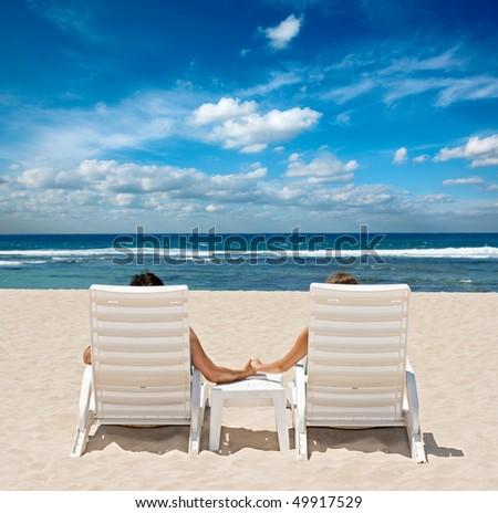 Honeymoon couple sunbathing in beach chairs - stock photo