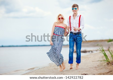 Honeymoon. Happy couple running on the beach. Sea trip of two sailors.